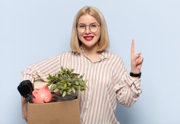 Femme blonde souriante et semblant amicale, montrant le numéro un ou le premier avec la main en avant, compte à rebours