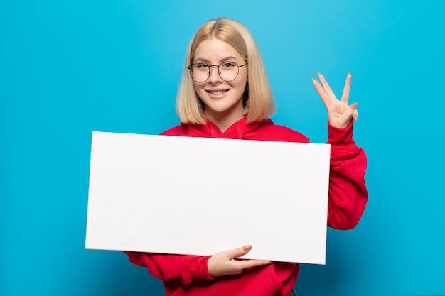 Femme blonde souriante et semblant amicale, montrant le numéro trois ou troisième avec la main vers l'avant, compte à rebours