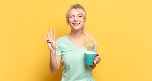 Femme blonde souriante et à la sympathique, montrant le numéro quatre ou quatrième avec la main en avant, compte à rebours