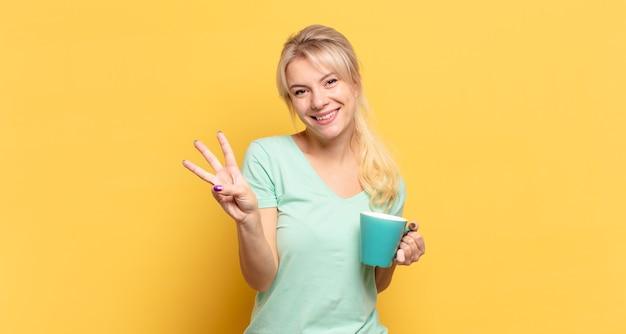 Femme blonde souriante et à la sympathique, montrant le numéro trois ou troisième avec la main en avant, compte à rebours