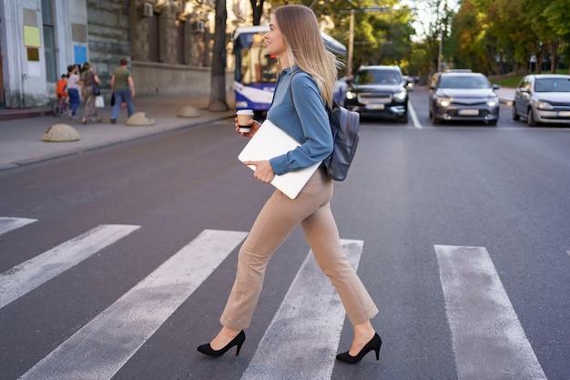 Femme blonde souriante traversant le zèbre avec café et ordinateur portable