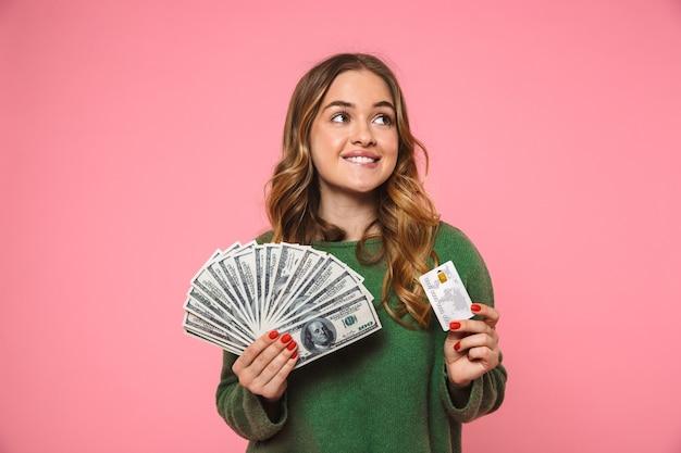 Femme blonde souriante vêtue d'un pull vert tenant de l'argent et une carte de crédit tout en regardant ailleurs par-dessus le mur rose