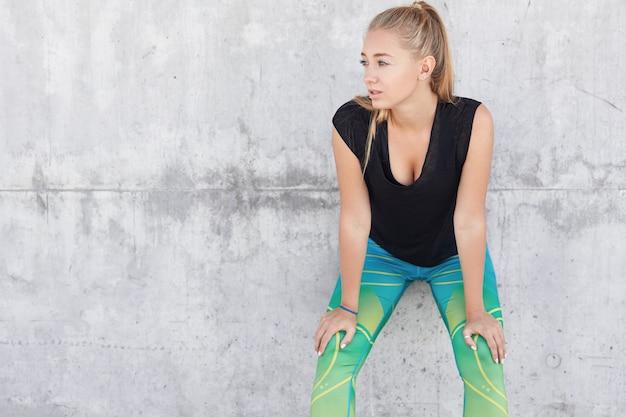Une femme blonde sportive reprend son souffle après le jogging