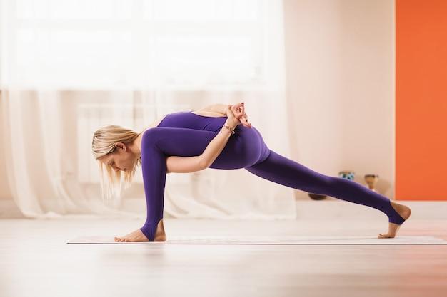 Femme blonde en sportswear bleu faisant du yoga effectue un exercice d'étirement dans une pièce près de la fenêtre