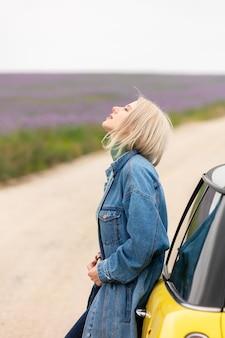Femme blonde de style avec une voiture près de fleurs déposées en automne