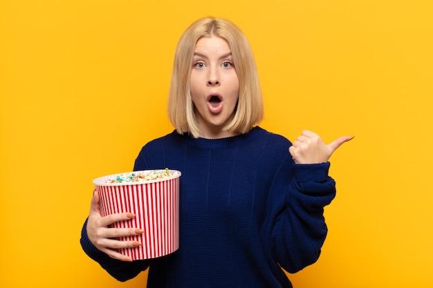 Femme blonde à la surprise de l'incrédulité, pointant sur l'objet sur le côté et disant wow, incroyable