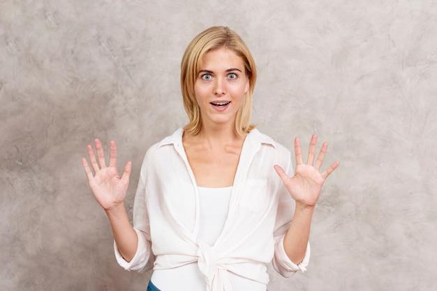 Femme blonde surprise avec les mains en l'air