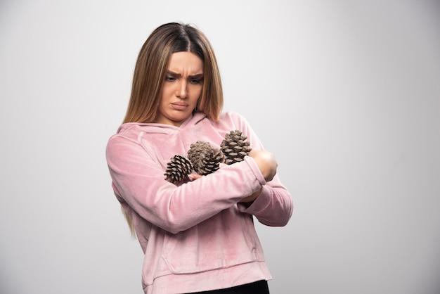 Une femme blonde en sweat-shirt rose fait un visage malheureux avec des cônes de chêne dans la main.