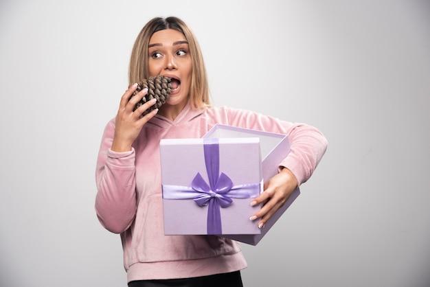 Une femme blonde en sweat-shirt rose sort un cône de chêne de la boîte-cadeau et se sent heureuse.
