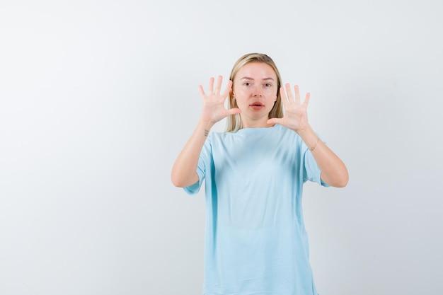Femme blonde en t-shirt bleu levant les paumes en geste de reddition et à la mignonne