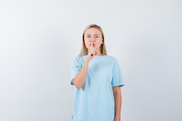 Femme blonde en t-shirt bleu montrant un geste de silence et semblant sérieux