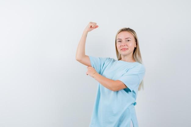 Femme blonde en t-shirt bleu montrant des muscles et semblant puissante