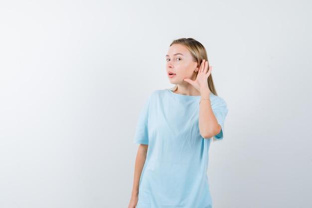 Femme blonde en t-shirt bleu tenant la main près de l'oreille pour entendre