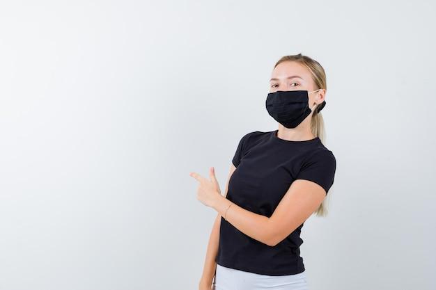 Femme blonde en t-shirt noir, pantalon blanc, masque noir pointant vers la gauche