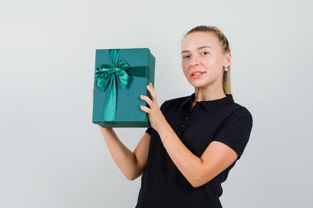 Femme blonde en t-shirt noir tenant une boîte-cadeau et souriant et à la recherche de plaisir