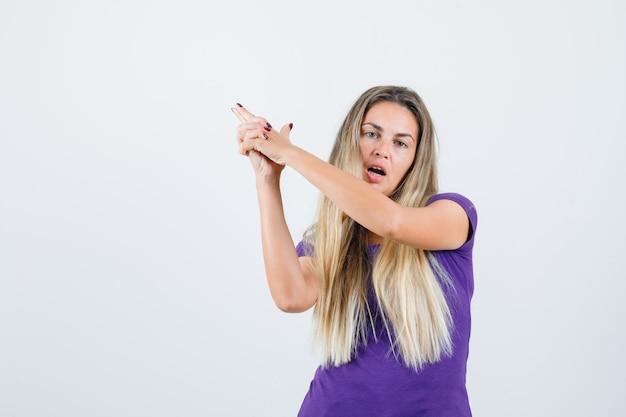 Femme blonde en t-shirt violet montrant le geste du pistolet et à la vue de face, confiant.