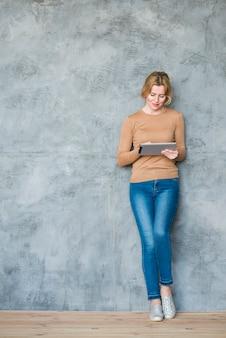 Femme blonde avec tablette au mur