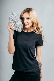 Femme blonde tenant beaucoup d'argent