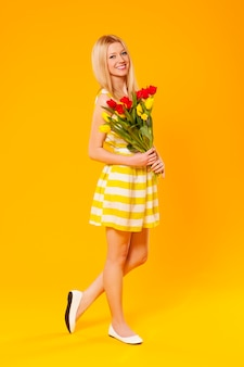 Femme blonde tenant un bouquet de fleurs de printemps