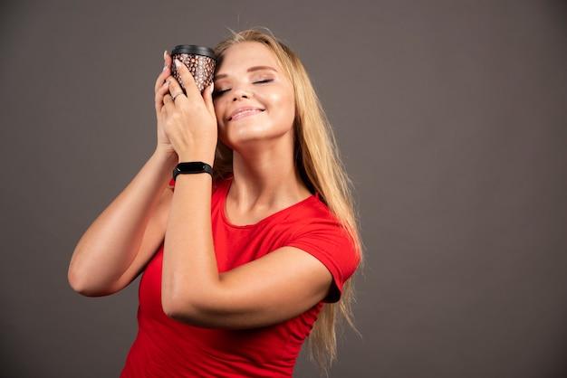 Femme blonde tenant un café à emporter avec une expression heureuse.