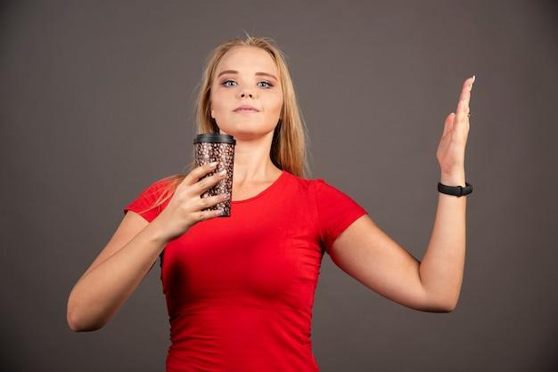 Femme blonde tenant un café à emporter sur un mur noir.