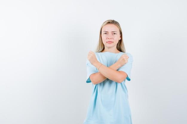 Femme blonde tenant deux bras croisés, ne faisant aucun signe