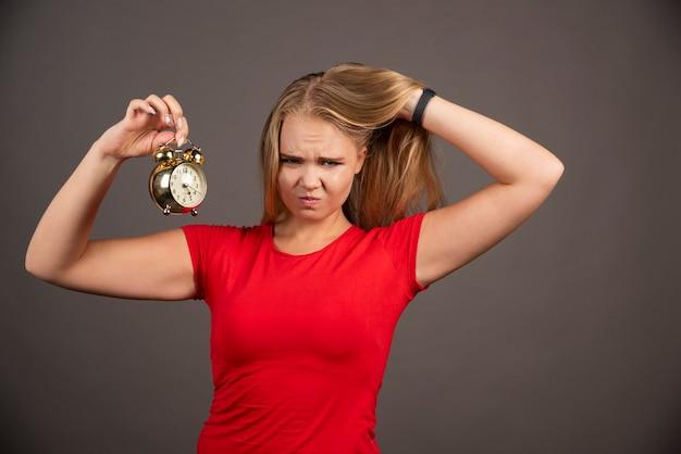 Femme blonde tenant une horloge sur un mur noir.