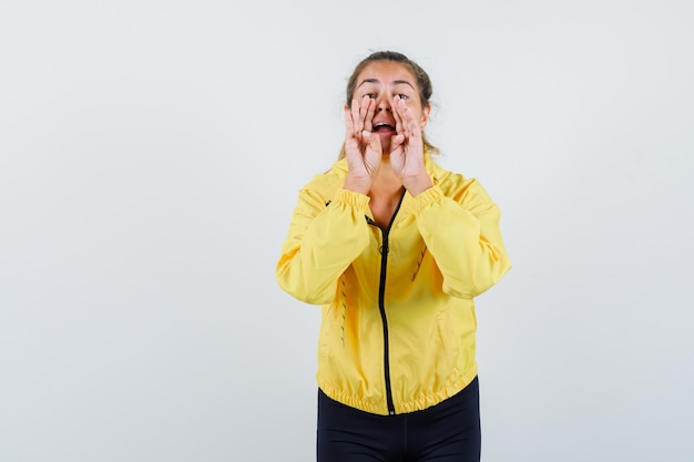 Femme blonde tenant la main près de la bouche comme appeler quelqu'un en blouson aviateur jaune et pantalon noir et à heureux