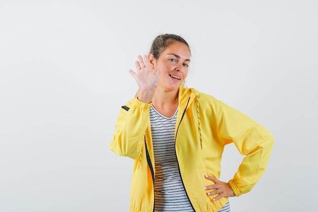Femme blonde tenant une main sur la taille tout en étirant une autre main pour saluer quelqu'un en blouson aviateur jaune et chemise rayée et à la joie