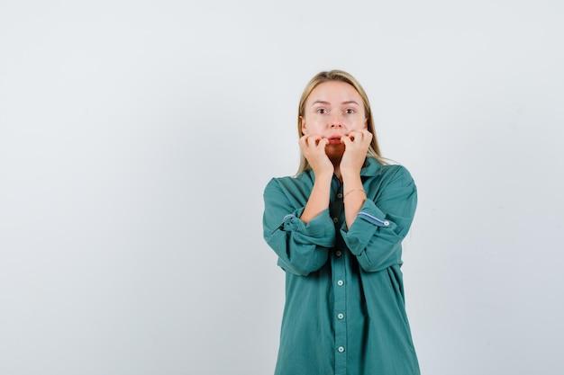 Femme blonde tenant les mains près de la bouche en chemise verte et à la peur
