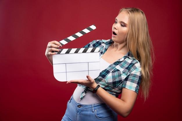 Femme blonde tenant un panneau de battant de production de film et a l'air confus et fatigué.