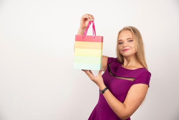 Femme blonde tenant un sac cadeau avec une expression heureuse.
