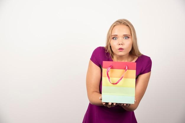 Femme blonde tenant un sac cadeau avec une expression surprise.