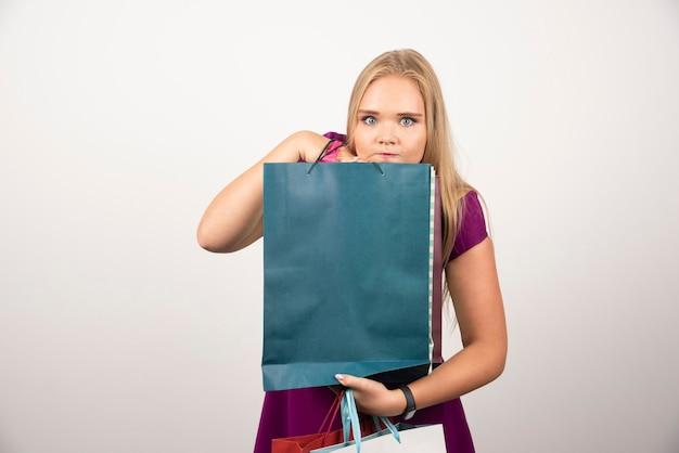 Femme blonde tenant des sacs à provisions sur blanc.