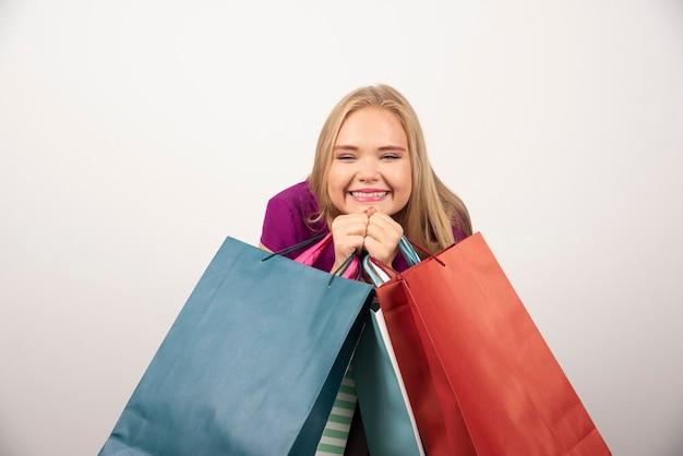 Femme blonde tenant des sacs à provisions avec une expression heureuse.