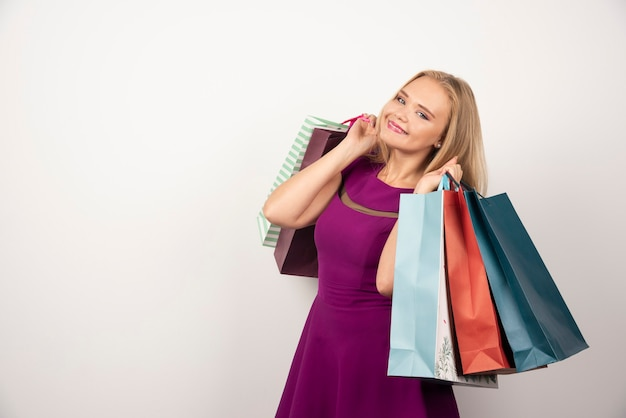 Femme blonde tenant un tas de sacs colorés.