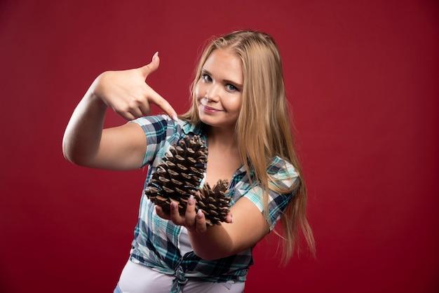 Une femme blonde tient un cône de chêne dans la main et a l'air positive et joyeuse.