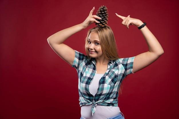Une femme blonde tient un cône de chêne à la tête et se sent positive.