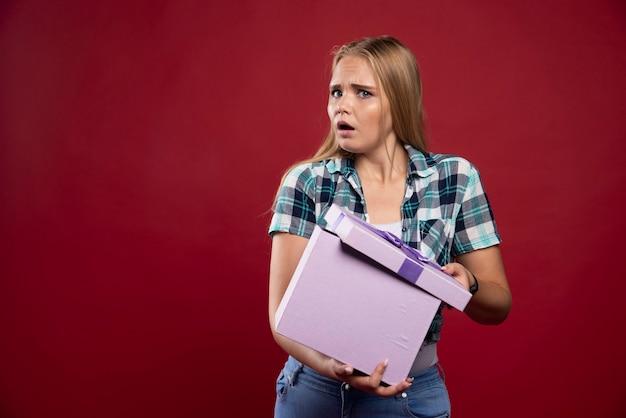 Une femme blonde tient fermement une boîte-cadeau et a l'air confuse et insatisfaite.