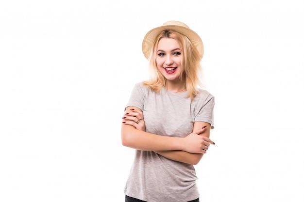 Femme blonde tient ses bras croisés devant le mur blanc