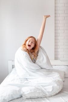 Femme blonde tout en s'étirant sur le lit après le réveil