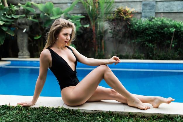 Femme blonde en train de bronzer et allongé sur le bord de la piscine sur une piscine à débordement dans un complexe tropical