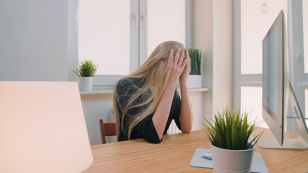 Femme blonde triste dans des vêtements élégants serrant la tête après un échec ou une mauvaise nouvelle assise dans un bureau léger...
