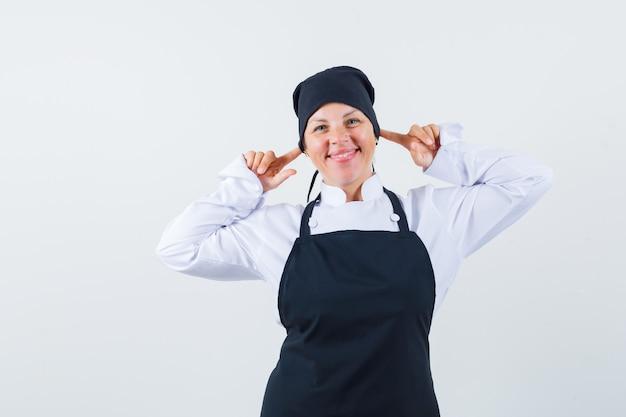 Femme blonde en uniforme de cuisinier noir, brancher les oreilles avec l'index et à la jolie vue de face.