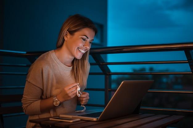Femme blonde utilisant un ordinateur tard dans la nuit. image iso élevée.
