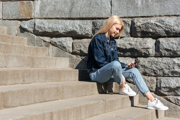 Femme blonde, utilisation, smartphone, et, écouteurs