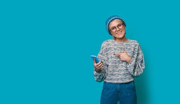 Femme blonde en vêtements bleus pointant vers son nouveau téléphone portant des lunettes sur un mur de studio avec espace libre