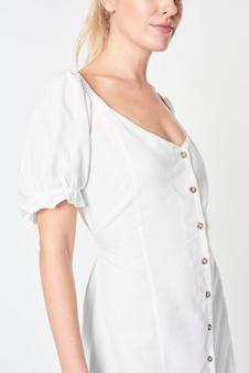Femme blonde vêtue d'une robe boutonnée blanche