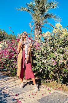 Une femme blonde vêtue d'un vêtement de style oriental posant et souriant sur un buisson de fleurs rose