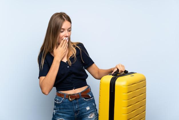 Femme blonde voyageur avec valise avec expression faciale surprise et choquée